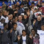 Naples' mayor Luigi De Magistris, center, poses for a photo with a group of refugees hosted by the city, during the Italian Serie A soccer match between Napoli and Lazio at the San Paolo stadium in Naples, Italy, Saturday, Nov. 5, 2016. (Ciro Fusco/ANSA via AP)