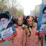 Two young girls hold the portraits of the leaders of the Iranian Revolution
