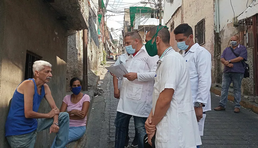 Venezuelan and Cuban doctors advise a person not waring a mask. April 2020